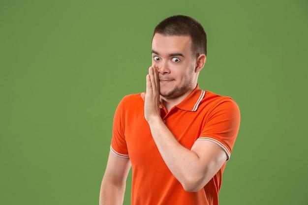 El joven susurrando un secreto detrás de su mano sobre verde