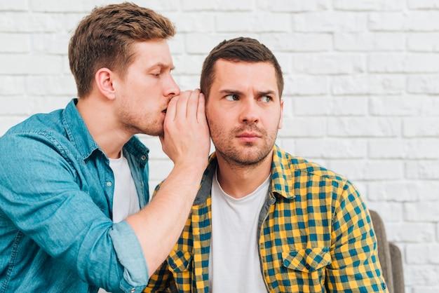 Joven susurrando un secreto en el oído de su amigo
