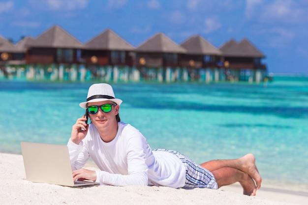Joven con tablet pc y teléfono celular en playa tropical