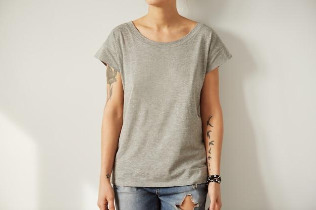 Joven tatuada vistiendo camiseta gris en blanco