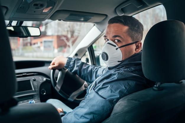 Joven taxista hispano con una máscara protectora y habla con un cliente.