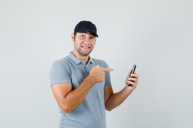 Joven técnico apuntando al teléfono móvil en uniforme gris y mirando alegre.
