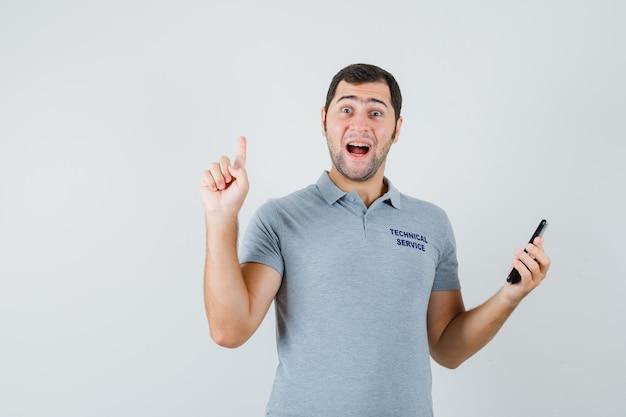 Joven técnico apuntando hacia arriba, sosteniendo el teléfono móvil en uniforme gris y mirando feliz.