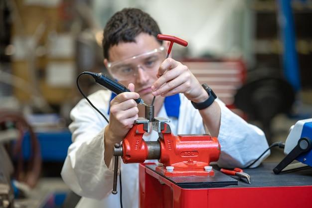 Joven técnico en una fábrica de reparación de una máquina. el hombre usa una prensa para trabajar en la fábrica