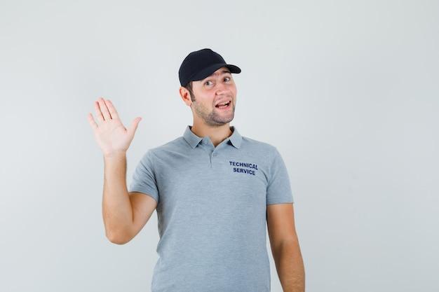 Joven técnico en uniforme gris agitando la mano para saludar y mirar alegre.
