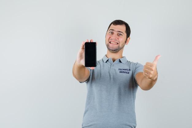 Joven técnico en uniforme gris sosteniendo el teléfono móvil, mostrando el pulgar hacia arriba y mirando alegre, vista frontal.