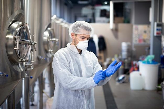 Joven tecnólogo poniéndose guantes de goma protectores en la fábrica de producción