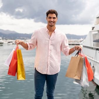 Joven teeanger mostrando sus bolsas de compras