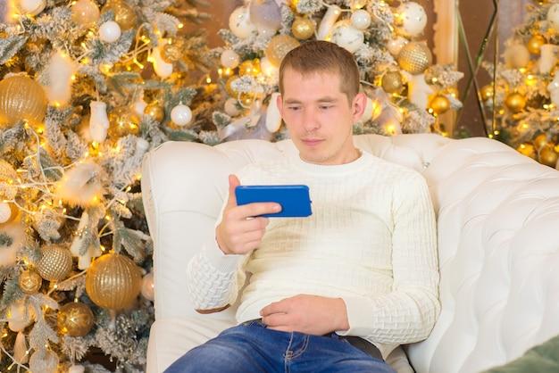 Joven con teléfono cerca del árbol de navidad en navidad