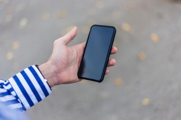 Joven con teléfono inteligente en la mano enviando mensajes de texto al aire libre en la calle