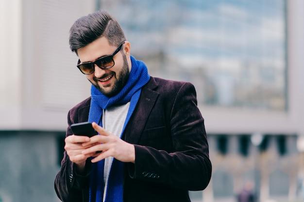 Joven con teléfono móvil en la calle