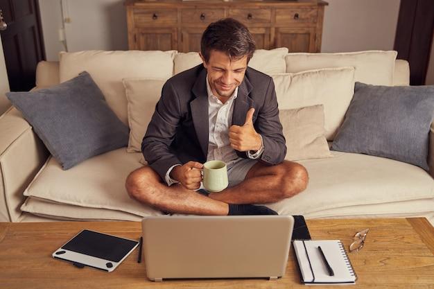Joven teletrabajando desde casa en videoconferencia, sentado en el sofá con traje y pantalones cortos. bebe café y hace un signo de me gusta con la mano.