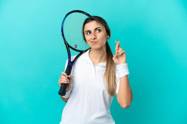 Joven tenista aislado sobre fondo azul con los dedos cruzando y deseando lo mejor