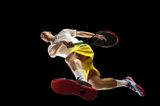 Joven tenista caucásico en acción, movimiento aislado en la pared negra, mira desde abajo. concepto de deporte, movimiento, energía y estilo de vida dinámico y saludable. entrenando, practicando.