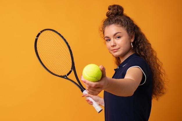 Joven tenista de pie con raqueta contra fondo amarillo