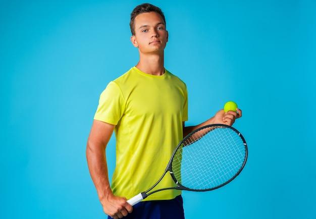 Joven tenista en ropa deportiva posando sobre fondo azul de cerca
