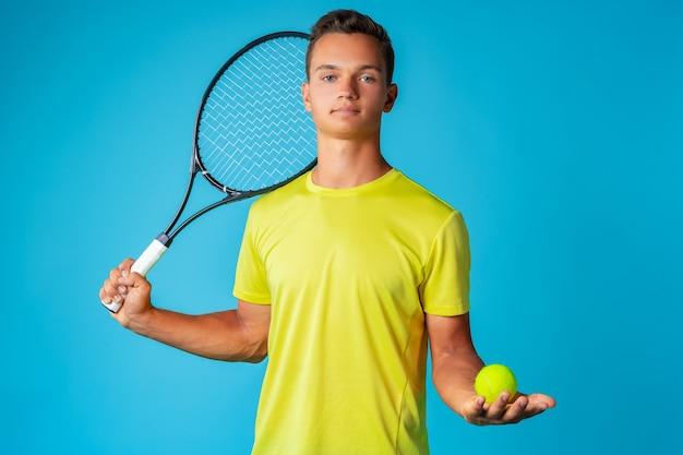 Joven tenista en ropa deportiva posando sobre fondo azul.