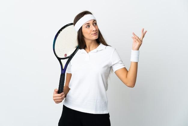 Joven tenista sobre blanco aislado extendiendo las manos hacia el lado para invitar a venir
