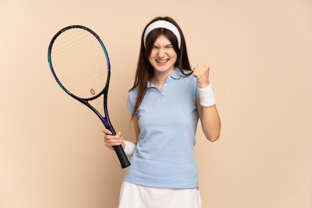 Joven tenista sobre pared aislada celebrando una victoria en la posición ganadora