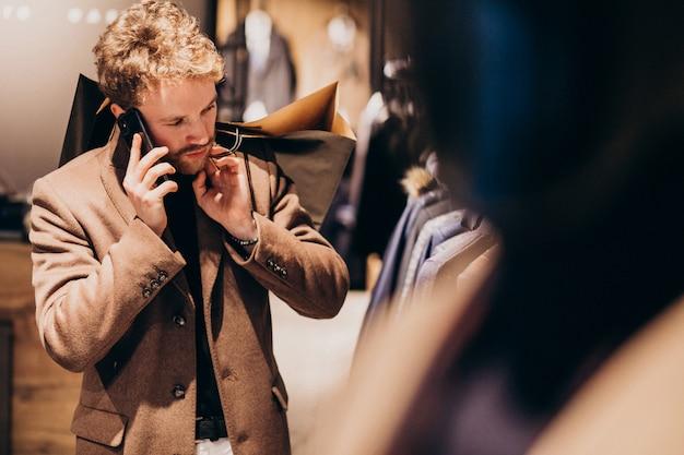 Joven en la tienda de ropa masculina hablando por teléfono