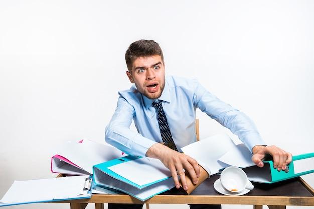 El joven tiene un completo desastre en el lugar de trabajo, no puede organizar su espacio.