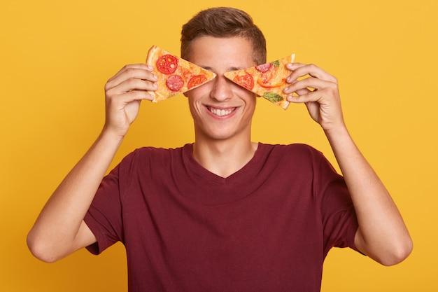 Joven tiene dos pedazos de pizza fresca en sus manos y cubriendo sus ojos con un sabroso producto, posando aislado sobre amarillo