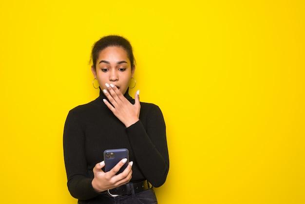 Joven tiene teléfono, feliz de recibir notificación. foto de chica latina viste ropa casual. concepto de emociones y sentimientos agradables.
