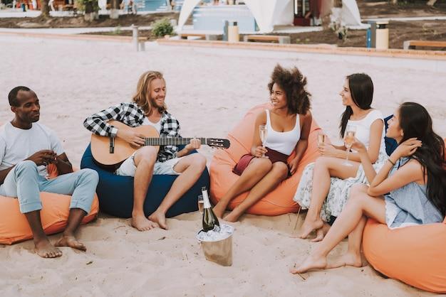 Joven tocando la guitarra para amigos multirraciales.