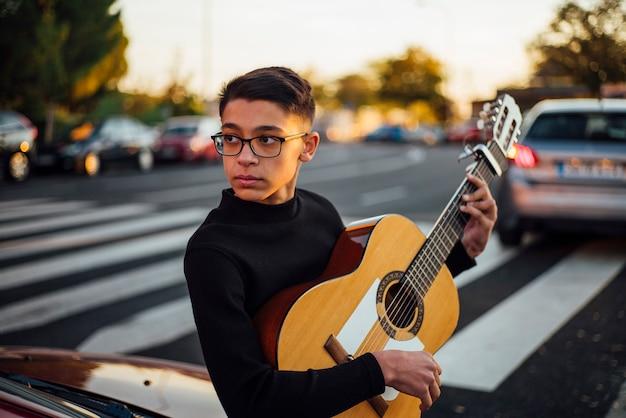 Joven tocando la guitarra por la ciudad de madrid, españa.
