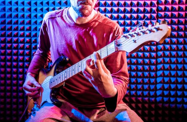 Joven tocando la guitarra en el estudio de grabación de sonido.
