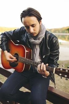 Joven tocando la guitarra en el lago