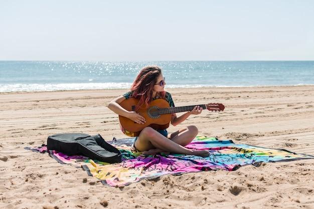 Joven tocando la guitarra en la playa