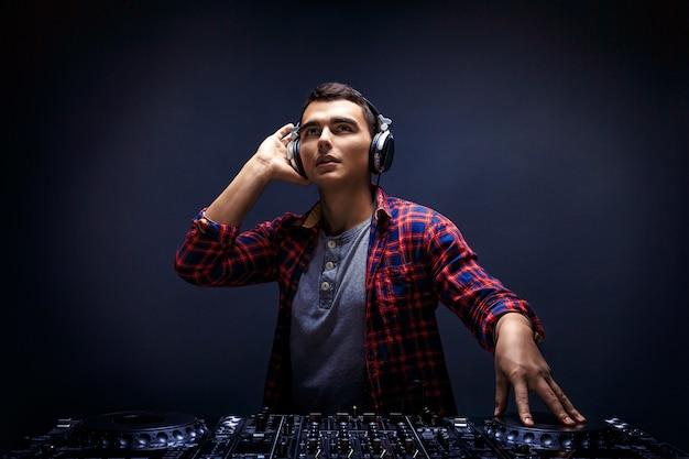 Joven tocar música en un mezclador de dj en studio
