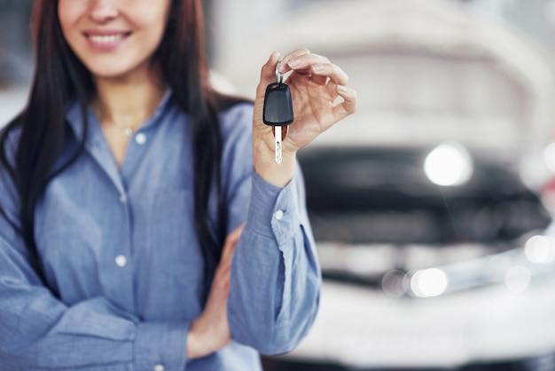 Una joven toma un automóvil del centro de servicio de automóviles. ella es feliz porque el trabajo está hecho perfectamente.