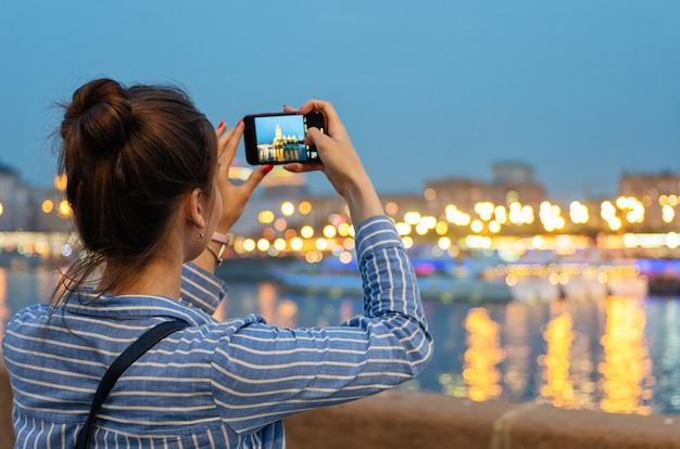 Una joven toma fotos de una ciudad nocturna con una cámara de teléfono celular.