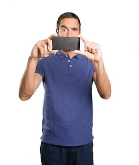 Joven tomando una foto con su teléfono móvil sobre fondo blanco