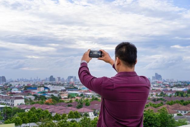 Joven tomando fotos del paisaje urbano con su teléfono celular