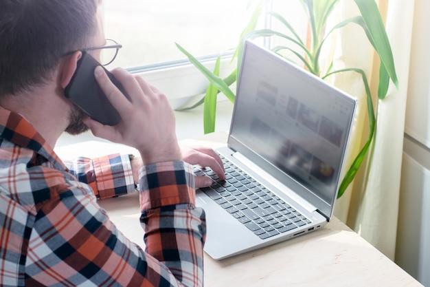 Joven trabaja en una computadora en casa. concepto de trabajo en línea desde casa. persona de libre dedicación. hacer negocios en casa