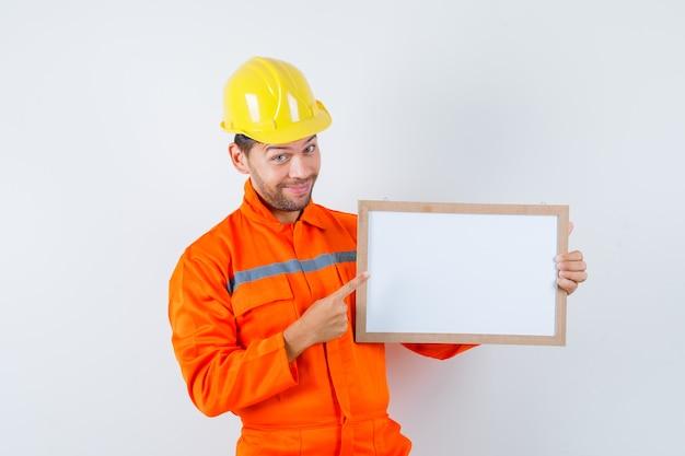 Joven trabajador apuntando al marco en blanco en uniforme, casco y mirando feliz.