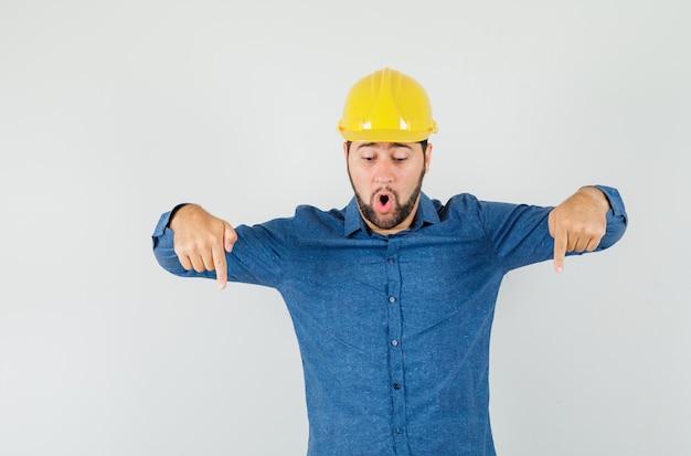 Joven trabajador apuntando con el dedo hacia abajo en camisa, casco y mirando sorprendido