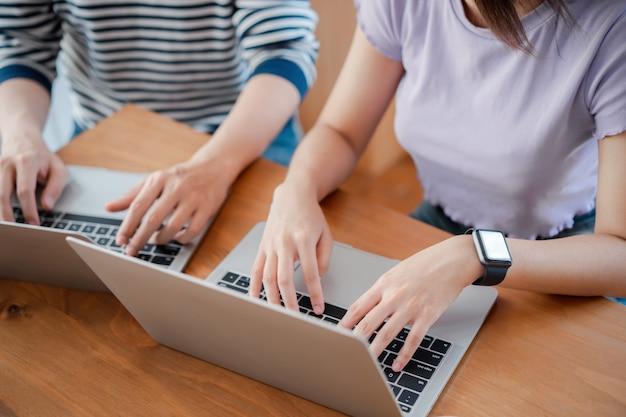 Joven trabajador asiático discutiendo juntos y escribiendo en la computadora durante el día de trabajo en la oficina en casa