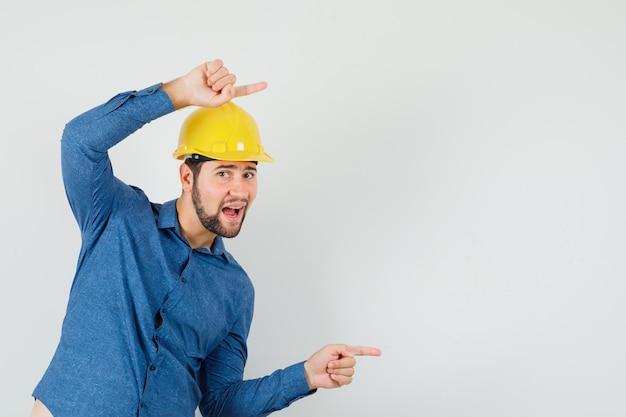 Joven trabajador en camisa, casco apuntando hacia un lado y mirando contento