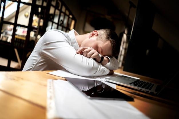 Joven trabajador cansado duerme en su lugar de trabajo, trabajo excesivo
