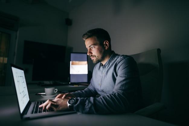 Joven trabajador caucásico escribiendo en la computadora portátil mientras está sentado en la oficina a altas horas de la noche