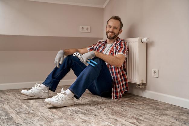Joven trabajador caucásico sentado en el piso con llave en mano