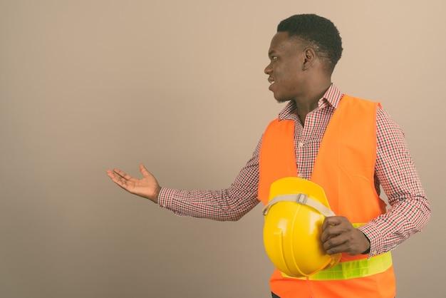Joven trabajador de la construcción africana mostrando algo