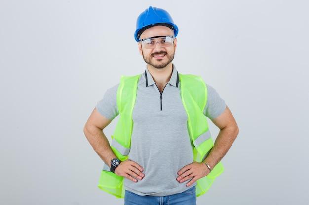 Joven trabajador de la construcción en un casco de seguridad y gafas