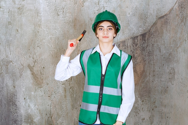 Joven trabajador de la construcción en casco verde posando con martillo