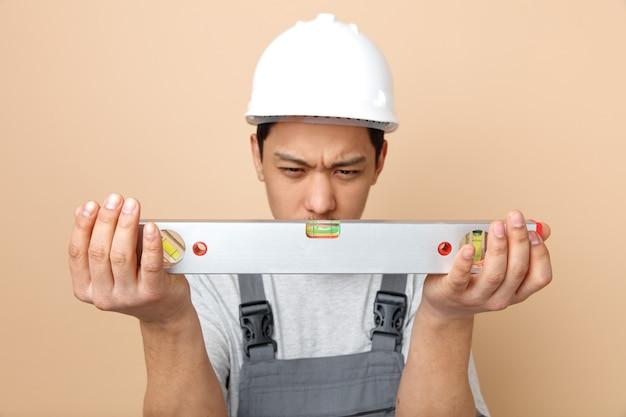 Joven trabajador de la construcción con el ceño fruncido con casco de seguridad y uniforme sosteniendo y mirando la regla de nivel