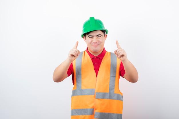 Joven trabajador de la construcción en chaleco de seguridad de pie y apuntando a algún lugar.